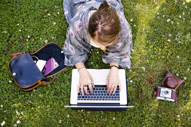 Happy woman using laptop at park — Stock Photo