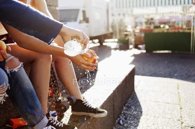 Jeunes filles lavant apple sur la rue — Photo de stock