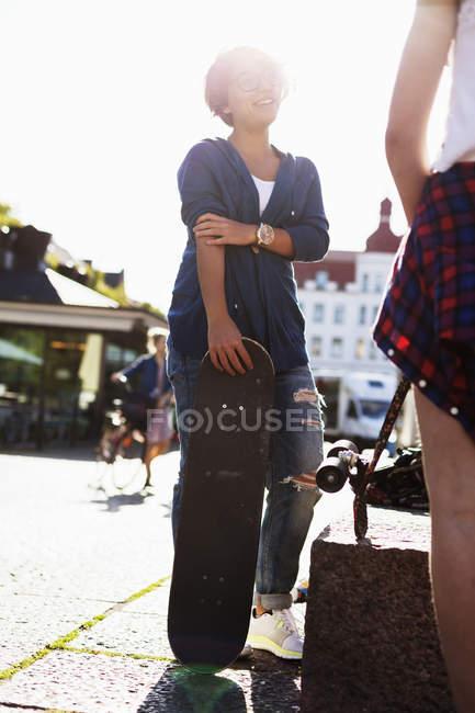 Ragazze in piedi con gli skate su strada — Foto stock