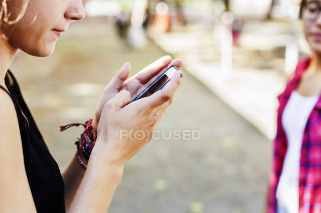 Girl using smartphone at footpath — Stock Photo