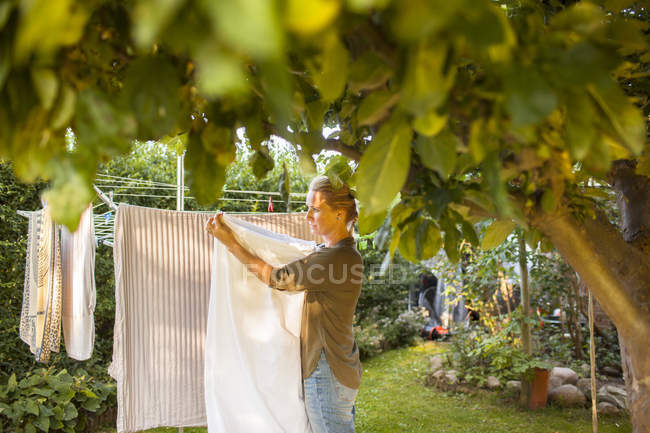 Woman hanging laundry on clothesline — Stock Photo