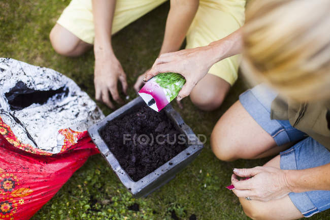 Mother and son pouring seeds into pot — Stock Photo