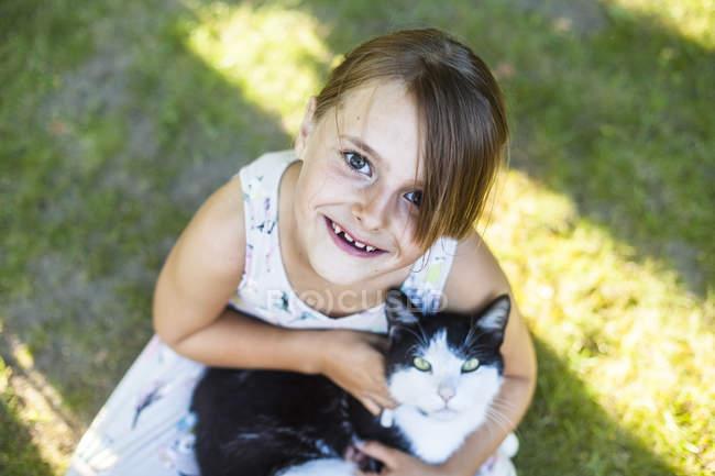 Девушка играет с котом на заднем дворе — стоковое фото