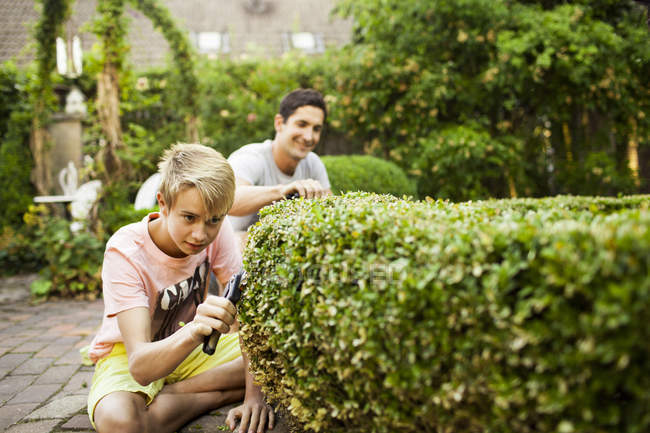 Boy pruning plant with father gardening — Stock Photo