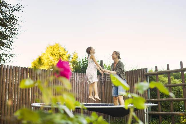 Mother and daughter jumping on trampoline — Stock Photo