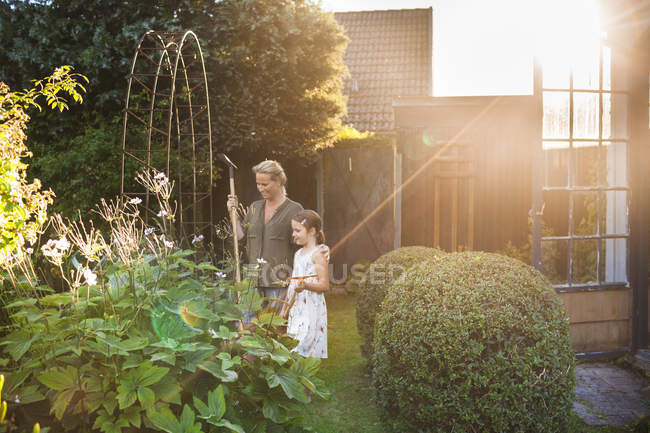 Mother and daughter standing in backyard — Stock Photo