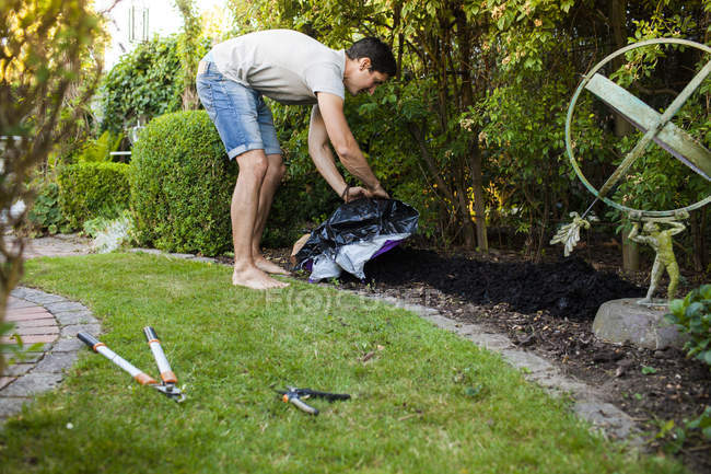 Man spreading fertilizer in garden — Stock Photo