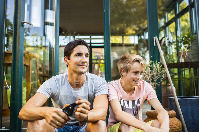 Father and son sitting outside house — Stock Photo