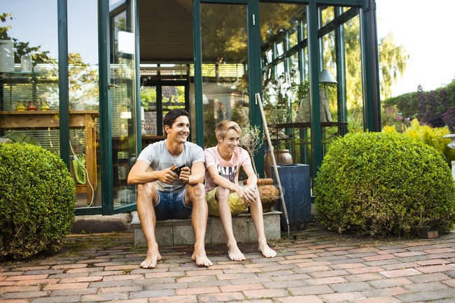 Father and son sitting outside — Stock Photo
