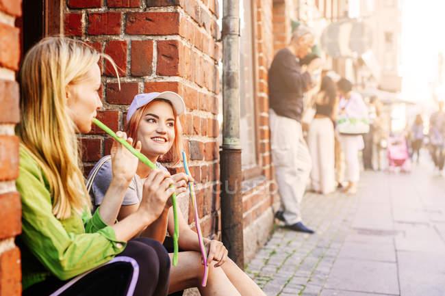Молодые женщины едят Конфеты лакричные — стоковое фото