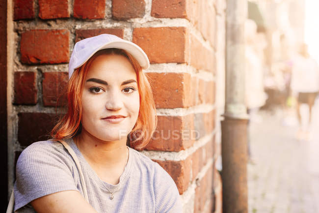 Young woman sitting by brick wall — Stock Photo