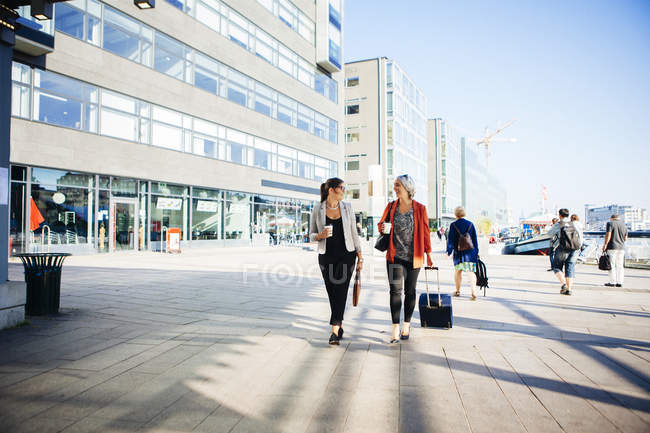 Businesswomen holding coffee cups and walking — Stock Photo