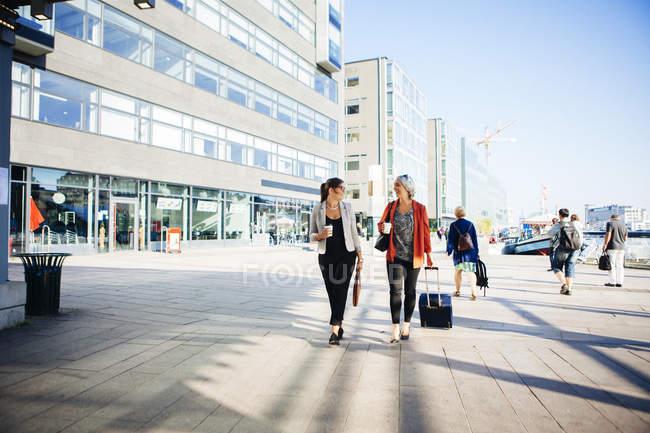 Empresarias sosteniendo tazas de café y caminando - foto de stock