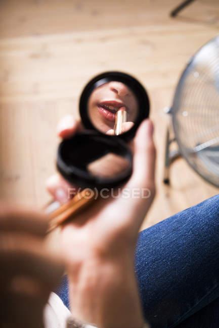 Reflection of fashion model applying lipstick — Stock Photo