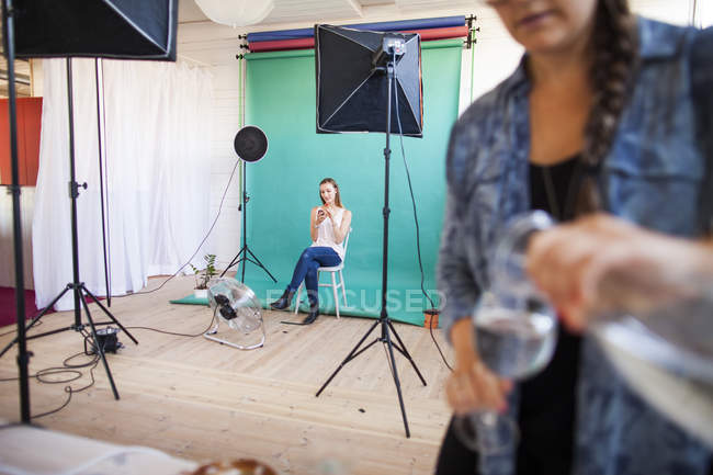 Фотоассистент наливает воду в стекло — стоковое фото