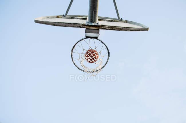 Aro de baloncesto y pelota contra cielo - foto de stock