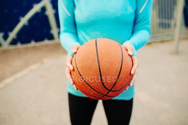Sporty woman holding basketball — Stock Photo