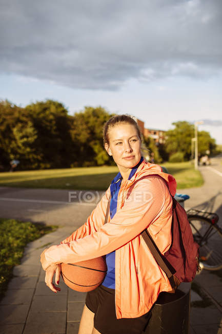 sporty woman holding basketball looking away lens flare stock