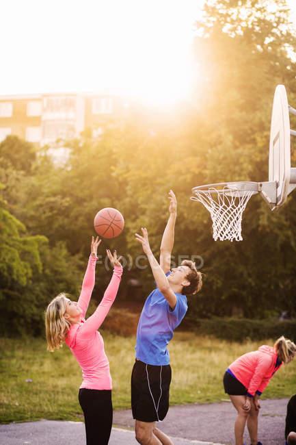 Друзья играют в баскетбол в парке — стоковое фото