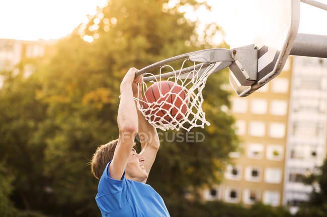 Boy doing slam dunk — Stock Photo