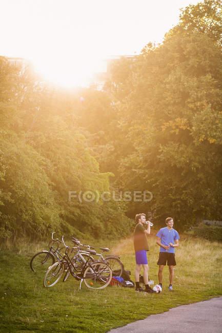 Чоловіків стоячи на велосипеді в парку — стокове фото