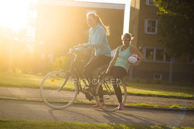 Women on bicycle with soccer ball — Stock Photo