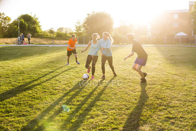 Friends playing soccer at park — Stock Photo