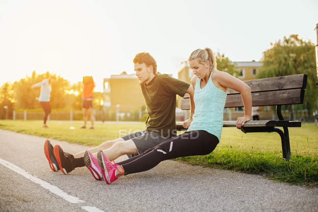 Girl and boy doing exercise on bench — Stock Photo