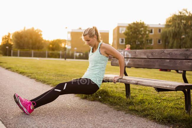 Fille faire de l'exercice sur le banc — Photo de stock