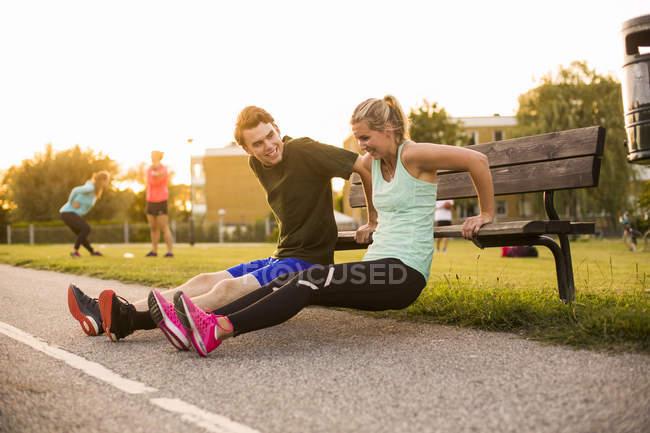 Menina e menino fazendo exercício no banco — Fotografia de Stock