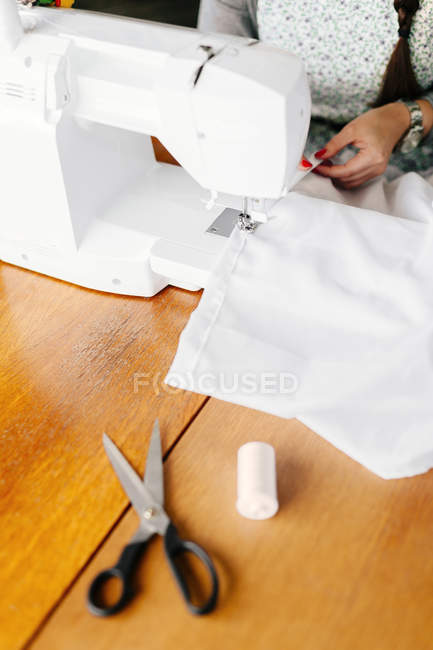 Fashion designer using sewing machine — Stock Photo
