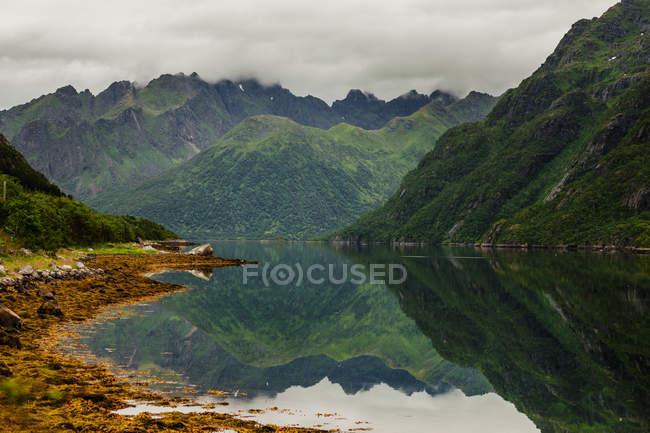 Montañas por el lago tranquilo - foto de stock