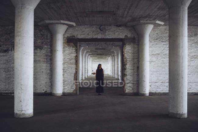 Woman standing in old factory — Stock Photo