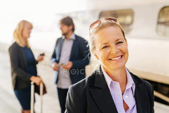 Счастливая бизнесвумен, стоящая на вокзале — стоковое фото