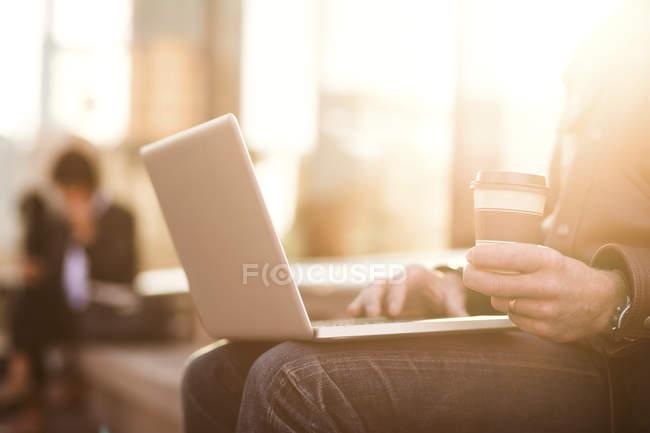 Midsection del hombre usando el ordenador portátil - foto de stock