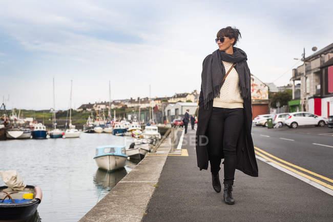 Femme marchant par le port — Photo de stock