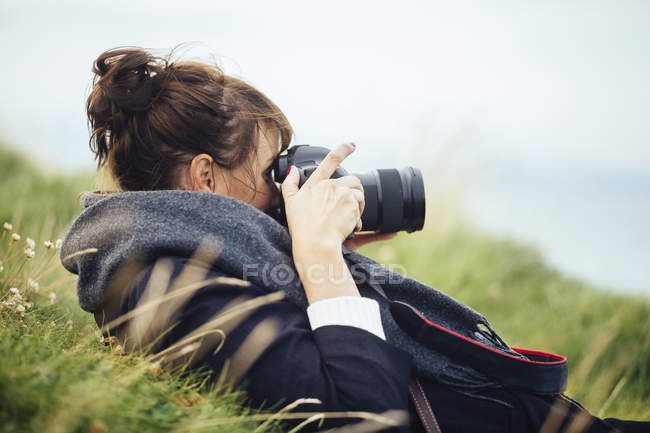 Woman photographing through SLR camera — Stock Photo