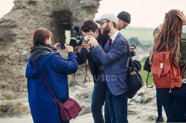 Men photographing woman holding smart phone — Stock Photo