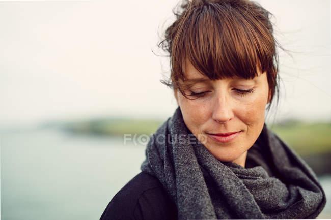 Mulher sorridente olhando para a praia — Fotografia de Stock