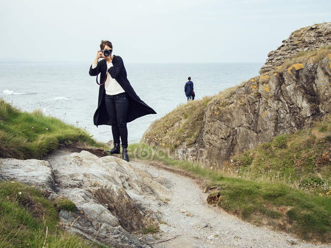 Woman photographing while standing on rock — Stock Photo