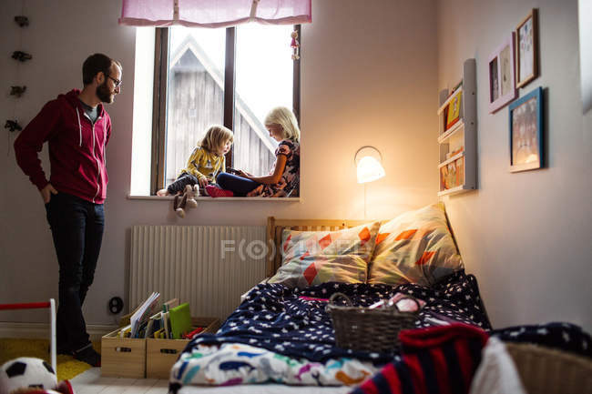 Mid adult man watching daughters — Stock Photo