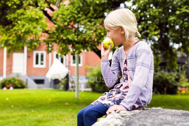Seitenansicht des Mädchens, das Apfel im Hof isst — Stockfoto