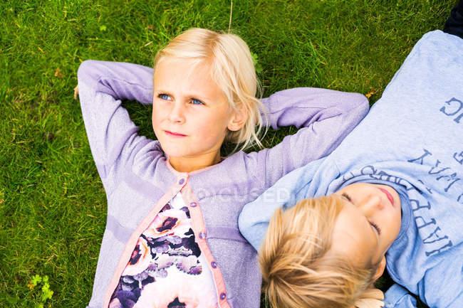 Дівчина з братом лежить на траві — стокове фото