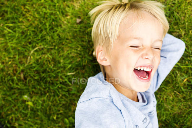 Boy laughing while lying on grass — Stock Photo