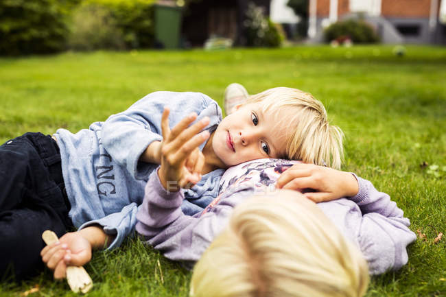 Boy lying on his sisters stomach — Stock Photo