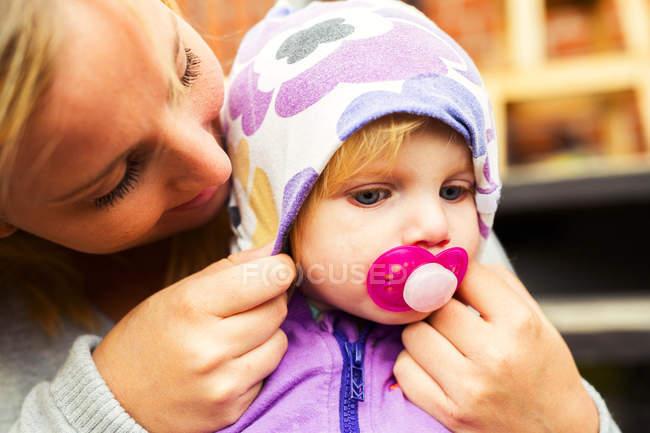Mother adjusting hood on babys head — Stock Photo