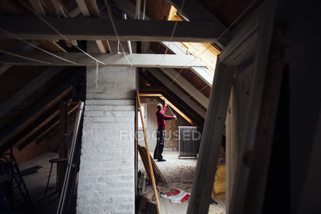 Man working in attic under construction — Stock Photo