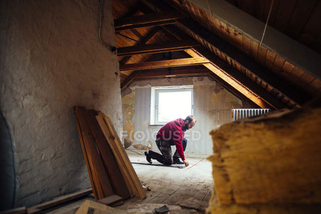 Man marking on floor in attic — Stock Photo