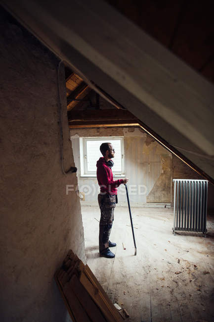 Man with work tool renovating attic — Stock Photo