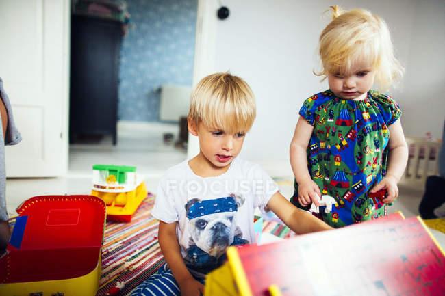 Брат і сестра, граючи з іграшками — стокове фото